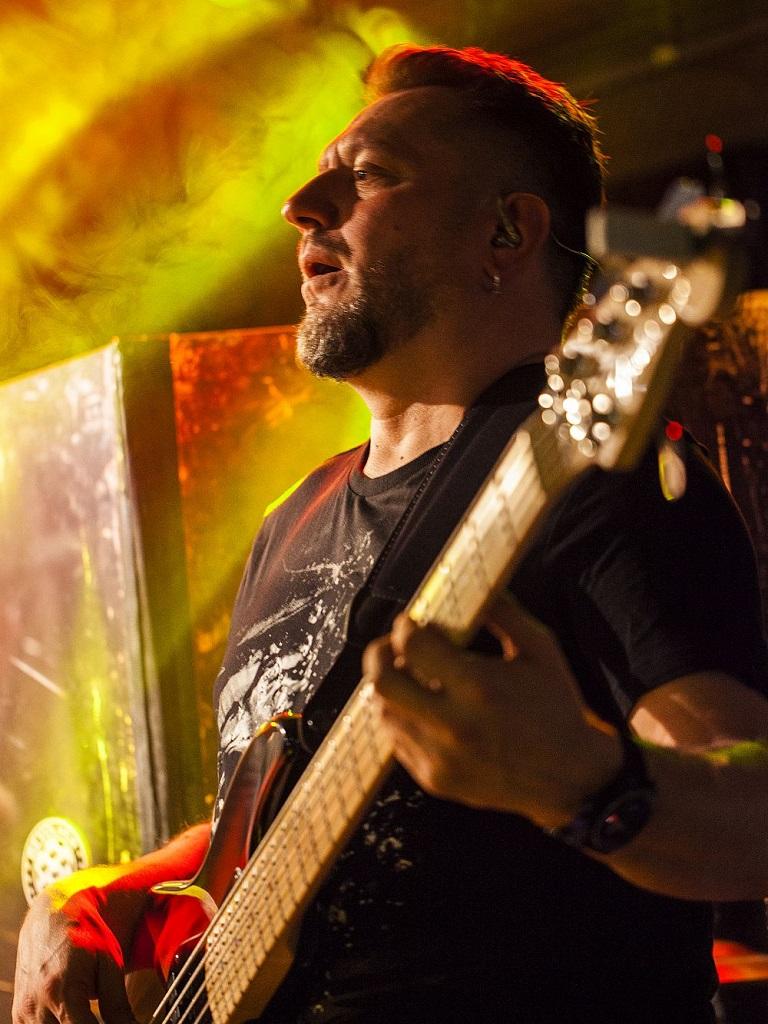 Piotr Rzempołuch gra na basie podczas występu zespołu coverowego z Warszawy True Colors Band w klubie Drukarnia na Pradze. Zdjęcie zrobione w trakcie piosenki It's My Life Bon Jovi w Drukarni na Pradze na corporate event.