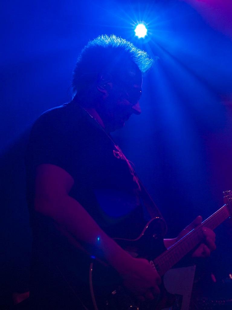 Waldemar Szoff podczas koncertu zespołu muzycznego z Warszawy True Colors Band w klubie Drukarnia na Pradze. Zdjęcie zrobione w trakcie solówki na gitarze elektrycznej do piosenki Beat It Michaela Jacksona.