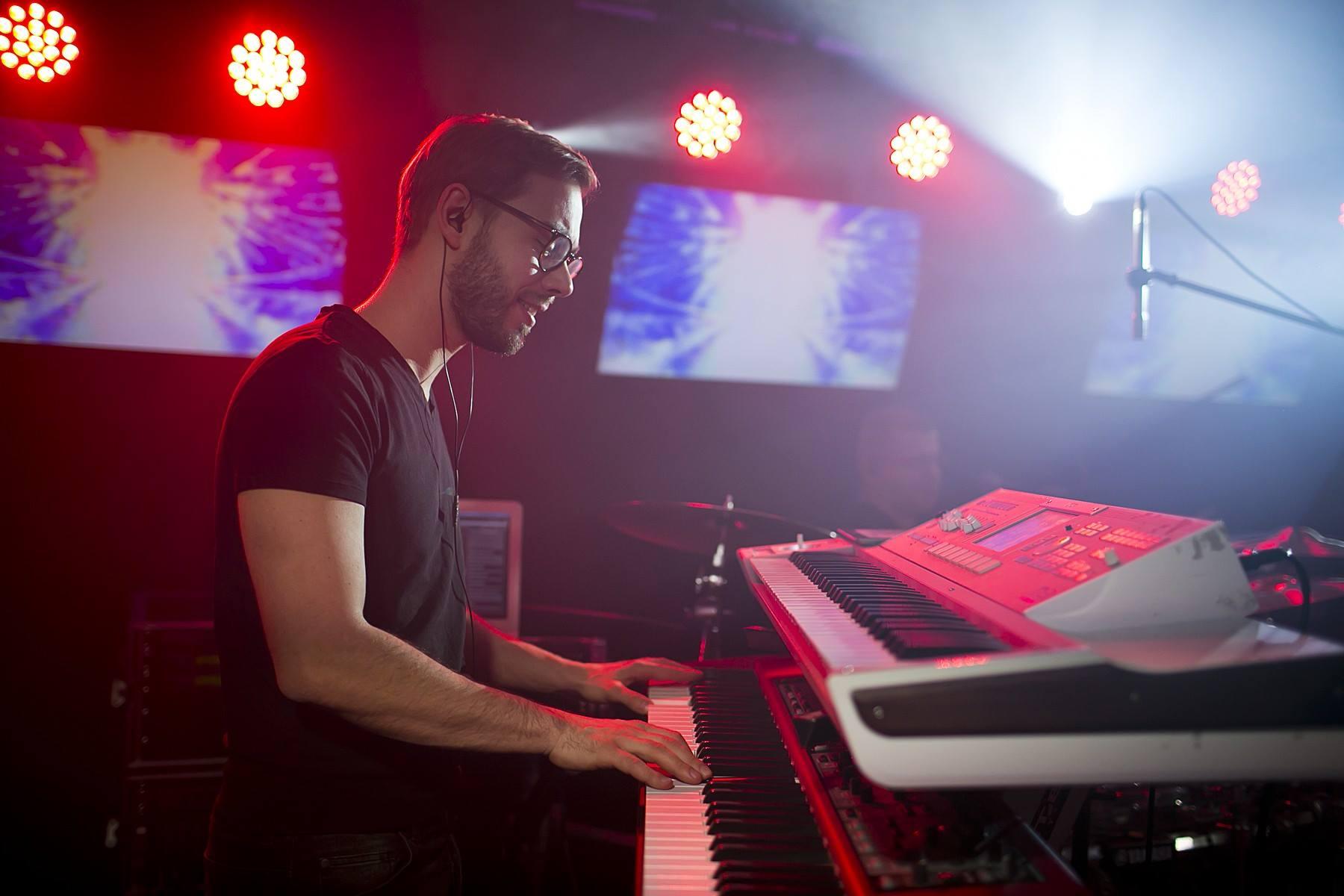 Paweł Jędrzejewski gra na klawiaturze.
